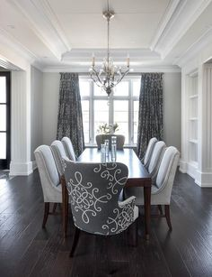 Gray dining room features a tray ceiling accented with a satin nickel and glass chandelier illuminating a dark stained curved dining table lined with dove gray velvet dining chairs as well as dark gray print wingback dining chairs placed atop a dark wood floor facing windows dressed in dark gray medallion curtains.