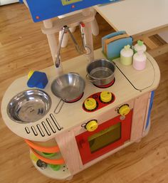 Great dramatic play layout with dress up, play kitchen, and book chair.