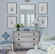 Blue beachy coastal living room design with vintage gray chest, pearl mirror, vertical art gallery, blue lamp, striped blue sofa, Suzanne Kasler Quatrefoil Chair and blue walls paint color. gray blue living room colors.