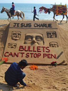 Indian artist Sudarsan Pattnaik is pictured with his sand sculpture, in tribute of those who lost their lives in the attack by gunmen on French satirical weekly Charlie Hebdo in Paris that killed 12 people, at Golden Sea Beach in Puri, some 65 kilometers from Bhubaneswar ASIT KUMAR/AFP/Getty Images