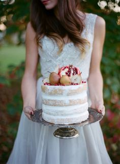 Naked cake topped with golden pears and a pomegranate