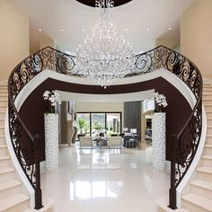 Would love this entryway one day! Obviously needs to be scaled back a bit - maybe white and wood stairs with a more modern light fixture in place of the gaudy chandelier. LOVE the shape of it though!