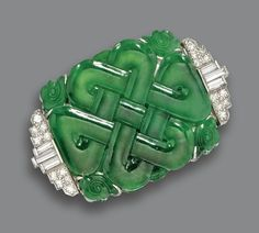 CARVED JADE AND DIAMOND BROOCH, CIRCA 1930.  The jade plaque carved with an intricate knot symbolizing luck, bordered by segments of baguette and single-cut diamonds at the sides, weighing a total of approximately 1.15 carats, mounted in platinum.