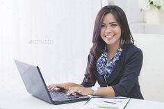 business woman using laptop by odua. portrait of happy asian business woman using laptop computer while working