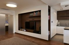 TV wall with bookcase flowing into kitchen