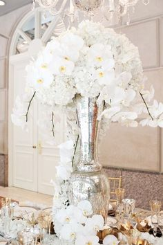 White orchids and hydrangeas in tall silver vase | photography by www.perezweddings.com/