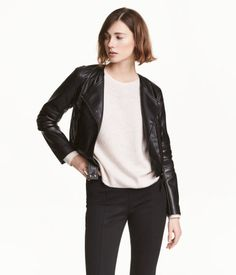 Black. Short jacket in imitation leather with lightly padded, quilted sections, diagonal zip, and tabs at hem with snap fasteners. Front pockets with zip