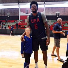 Olympic gymnast poses with basketball player.