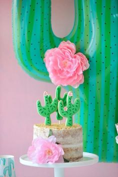 Cactus inspired children's birthday party cake. Naked white frosting decorated with edible desert sand and cookie toppers. Large green cactus balloon party decor. Cactus Party styling by Happy Wish Company. Photography by Tammy Hughes Photography. Stationery by Minted artist, Baumbirdy.