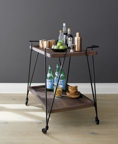 Prost rolls out functional drink service in a clean, contemporary style. This classic drink cart, framed gracefully in iron, takes warm shesham wood trays for a ride on smooth-rolling casters and curbed metal corners that make steering a breeze.