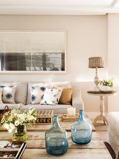 00438215. Sofá con cojines en blanco y azul. Mesa de centro de madera natural, jarrones azules, auxiliar con lámpara y cuadro 00438215