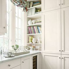 Timeless Shaker-Style Cabinets | Shaker-style cabinets mixed with open shelves (for cookbooks and dishes) provide plenty of storage. The timeless look of the white palette ensures the homeowners will enjoy the space for many years to come. | SouthernLiving.com