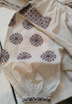 Embroidery design on a female shirt. There is a deliberate mistake in the pattern (the very right flowery ornament has a blank circle instead of a red one). There is a tradition in Ukraine to make a small mistake in the embroidery pattern on one of the sleeves of the bridal shirt. This mistake is very important. People believed that if a witch came to the wedding to cast a black spell or just wish a bad luck, the mistake on a shirt caught her eye and confused her. That's why you can often…