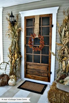 Love this screen door/ cat of nine tails, corn stalks, wide burlap and great wreath,
