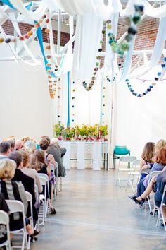 挙式会場にテーマカラーに合わせたリボンを渡す。屋根にバージンロードのイメージ。