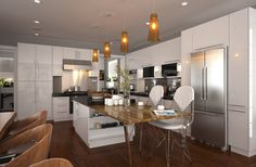 White lacquer is the main style of this kitchen, which presents a fashionable and elegant look. The combination of wall cabinets, base cabinets and high cabinets provides great storage place in kitchen. Besides, the L-shape layout with an island makes the kitchen look more spacious.