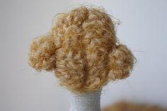 Os muestro cómo hacer un pelo recogido en moñetes para una Tilda. Empezamos por poner una fila de alfileres a la mitad de la cabeza y a ...