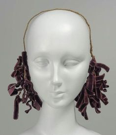 Woman's headdress, French, worn in Boston, mid 19th century. MFA, 51.376. Woman's headdress; band of wire wrapped in dark olive-green silk tape across top of head with massed loops of dark purple velvet ribbon at ends.