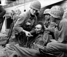 A US GI gives a wounded German POW water from his own canteen