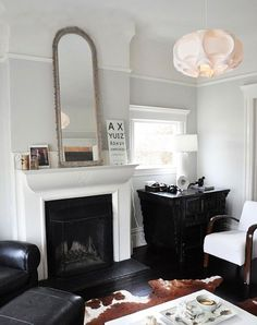 Faded gray walls, high ceiling with low molding, mantle - love the soft rose looking light shade more than anything.
