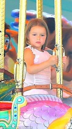 Holding on tight: Harper didn't let go of the pole as she rode around a carousel on a fish-shaped carriage