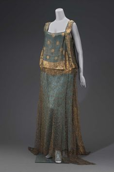 • Woman's evening dress.  Date: First quarter 20th century  Place of origin: United States  Medium: Silk brocaded with gold metallic yarns, silk satin, silk tulle, and metal snaps.