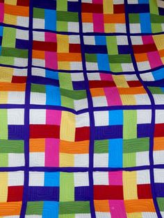 woven stripes quilt......or a disappearing Nine-patch with thin sashing.  Love the bright colors.