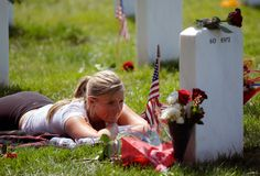 Stephanie Montgomery of Atlanta, Georgia, lies on the ground while visiting her brother's grave, Army Staff Sgt. Thaddeus Montgomery, 29, in Section 60 at Arlington National Cemetery in Arlington, Virginia, on May 28, 2012. Sgt. Montgomery died January 20 at Korengal Outpost, Afghanistan. (AP Photo/Cliff Owen)