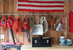 A plumbing pipe mounted along the wall holds yard work essentials on kitchen pot hooks.