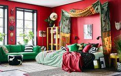 Tekstiler i kraftige farger, fargerike møbler og røde vegger gir dette soverommet en særpreget stil.