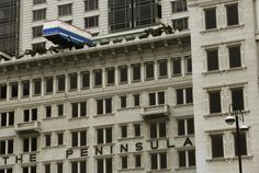 "An installation, ""Hang On a Minute Lads, I've Got a Great Idea"" by British artist Richard Wilson, is displayed at The Peninsula hotel in Hong Kong March 11, 2015. The installation, which uses a full-sized replica coach balanced on top of the hotel's older section, is based on a scene from the movie ""The Italian Job"". REUTERS/Bobby Yip"