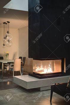 chimenea de cristal con el fuego ardiente dentro de una chimenea y negro en el fondo hay una mesa co Foto de archivo