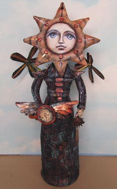 """Connie  The gown of this intriguing 16"""" painted muslin stumpdoll has a heavy, armored look embellished with stencils and stamps. Cardboard, muffler tape, brass tubing and a wooden spool form the propellers that take her on her celestial journeys."""