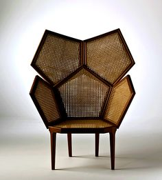 Highly stylised high back armchair fully canned available in single or double cane. This piece is characterized by the highly stylised sculptural profile and the cross references between the pentagon design and the use of cane emphasizing the geometric design ethos. Outstanding craftsmanship in relation to the application and or use of cane.