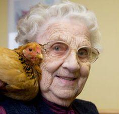 Ein Huhn auf der Schulter einer alten Dame