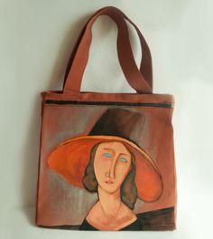 Ręcznie malowana torebka wykonana w pojedynczym egzemplarzu. Torebkę zdobi autorskie malowidło, kobieta w kapeluszu, wykonane trwałymi farbami, utrwalone w wysokiej temperaturze.  Torebka usztywnia, zachowująca swój pierwotny kształt, mieści format A4.  Torebkę można nosić na ramieniu i w ręce. Zapina na suwak, posiada wewnętrzną kieszonkę.  W razie potrzeby torebkę można przepraż ręcznie lub w pralce w temperaturze 30st. na niewielkim wirowaniu