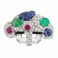 Art Deco Platinum, Diamond, Rock Crystal, Gem-Set, Carved Colored Stone and Black Enamel 'Tutti Frutti' Clip-Brooch, Ellis Bros.