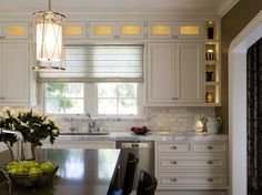 Love the backsplash and white cabinets. The lighted cabinets give it polish! Nice wall color too.