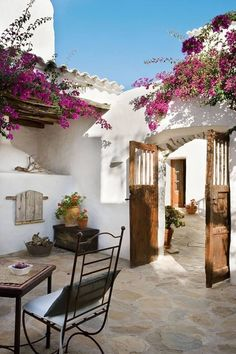 Sunny and charming Mediterranean-style patio courtyard, covered in blooming pink bougainvillea.