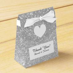 Silver glitter luxury style wedding favor box Faux silver glittery luxury style wedding favor box with personalized text thanking guests. Custom thank you message from bride and groom. Golden print with sparkly sparkles and glimmers plus elegant white ribbon bow. Customizable text. Luxury chic theme design with stylish typography and heart. Great for fancy wedding anniversary or bridal shower too. Silvery texture design. #wedding #favor #thank #you #glitter #heart #luxury #glamorous #sparkly…