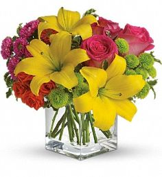 Hot pink roses, orange spray roses, yellow asiatic lilies, hot pink matsumoto asters and green button spray chrysanthemums are delivered in a cube vase. Lots of splash. Not too much cash!