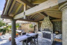 cuisine extérieure rustique: terrasse en pierre et toiture en bois