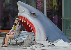 A tourist sits next to a sculpture of a shark in a shopping mall in Bangkok on Monday. Photo by Pornchai Kittiwongsakul/AFP/Getty Images.