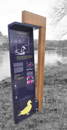 Outdoor freestanding information pylon sign at Lac de Louvain-la-Neuve by Traces…