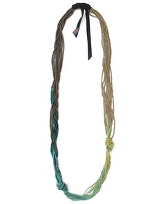 A hand beaded necklace made of knotted & loosely braided strands of seed & 2-cut beads in silver, mint, citrine, aqua, teal & pewter. Finished with soft grey leather ties.
