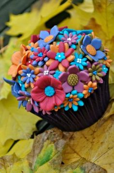 Adorable. Simple, cartoon-like flowers (these are probably fondant, maybe gumpaste - but white modeling chocolate would be great,) completely covering the cupcake. Would be really cute in spring colors, too.