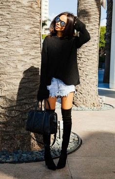 Street style look suéter preto, shorts jeans, bota over the knee e bolsa preta.