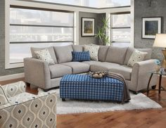 This Sectional from Fusion Furniture offers a beautiful casual, contemporary style. It features tapered arms, padded back pillows, box style seat cushions and exposed tapered feet. It is adorned with beautiful welting details. Gray polyester material with turquoise accent pillows. This Sectional is composed of a LAF Sofa and RAF Loveseat.