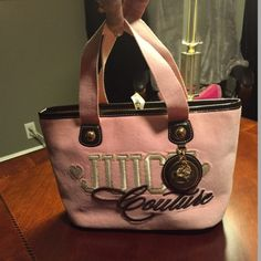 🎄🎁CCO 10% Bubblegum Pink Juicy Couture Tote Velvet exterior, tan interior w/pink Juicy Couture crown emblem & writing. Has zipper pocket on 1 side & a small open pocket on the other. Bottom of dark brown leather. Gross grain ribbon to tie the top closed. Never used in excellent condition, no scuffs, scrapes or marks. Pictures are best description, but any questions please ask. 💟 PRICE FIRM/NO BUNDLE DISCOUNT 💟 pd168*25 Juicy Couture Bags Totes