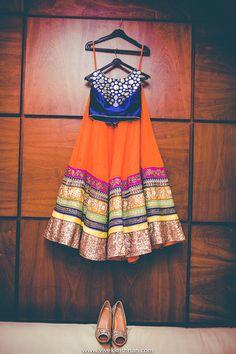 royal blue blouse, metallic work, orange lehenga, multicolored border, lehenga on a hanger shot, hanging lehenga shot